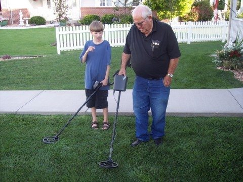 Grandpa and grandson are comparing their metal detectors and looking for old coins in the ground